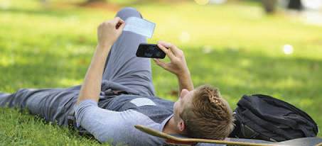 Man laying in the grass on a skateboard taking a photo of a check with his mobile device